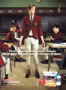 """Lunchables Uploaded Print Ad; Image shows boy standing in middle of math classroom wearing a private school uniform that is too small on him. Text overlay reads: """"They're outgrowing most things; their food doesn't have to be one of them.""""  Product shot including sandwich, drink, and snack are on bottom right corner."""